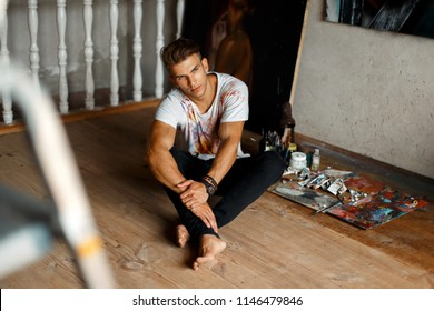 handsome young stylish man in a white T-shirt sits in an art studio. Artist