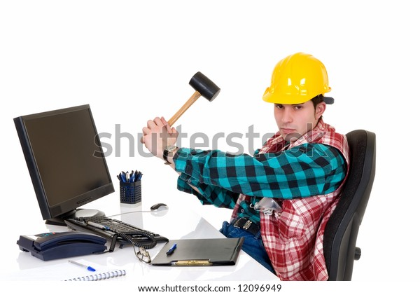 Handsome young successful  angry construction supervisor in the office, hitting sledge hammer on computer,  white background,  studio shot.
