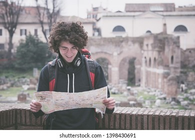 Handsome young tourist looking at tourist map