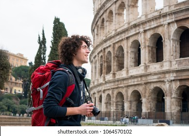 Handsome young tourist man with curly hair with a camera and backpack taking pictures of Colosseum in Rome, Italy. Young tourist taking pictures of Colosseum