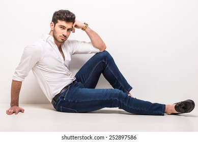 Handsome, young, trendy man is sitting on the floor in studio on gray background.