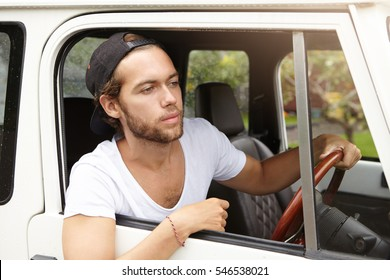 3874b1e3e52 Handsome young unshaven man wearing casual t-shirt and baseball cap  backwards looking out of