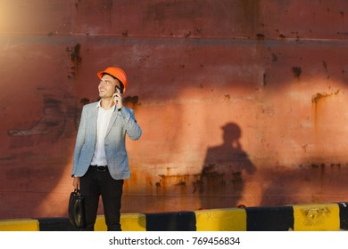 Handsome young unshaven successful business man in gray suit and protective construction orange helmet holding case, talking on mobile phone, standing in sea port against cargo rusty ship background.