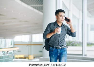 Handsome young Vietnamese man with backpack carrying cup of take away coffee and talking on phone when standing in office building
