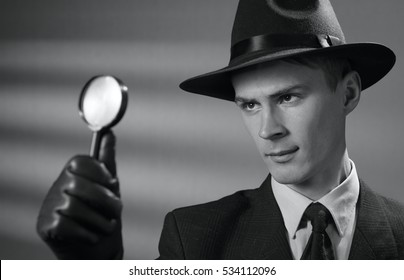 Handsome young vintage detective wearing a hat holding a magnifying glass in his gloved hand as he searches for clues, black and white portrait
