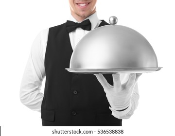 Handsome young waiter with cloche and tray on white background