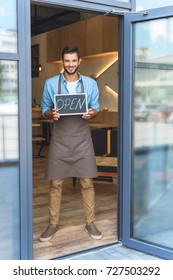 handsome young waiter holding open sign and smiling at camera