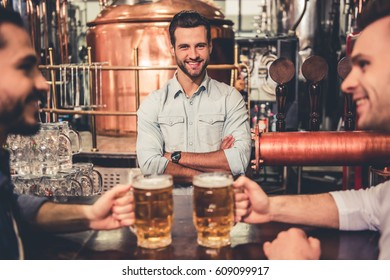 Handsome young waiter is looking at camera and smiling while working in pub