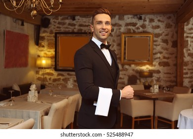 Handsome young waiter at restaurant