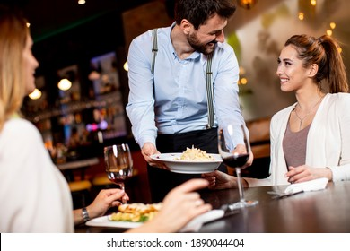 Handsome young waiter serving food to female customers in the restaurant