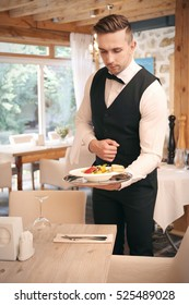 Handsome young waiter serving meals at restaurant