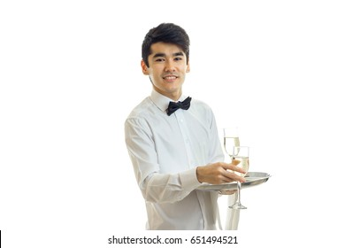 handsome young waiter smiles and keeps wine glasses on a tray that