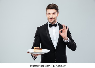 Handsome young waiter in tuxedo with bow tie holding plate with cake and showing ok sign over white background