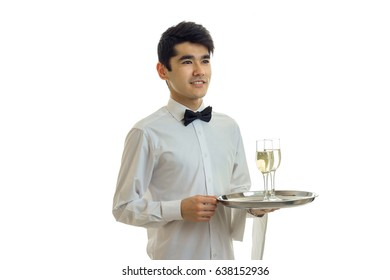 handsome young waiter's shirt smiling and holding a tray with glasses of wine