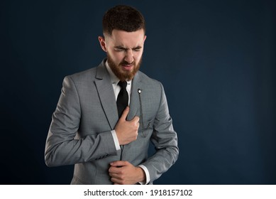 Handsome young white collar worker with chest pain wearing a grey jacket