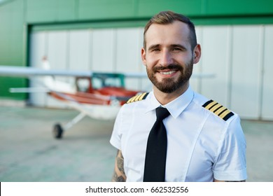 Handsome young white man pilot posing at the hangar with private motor airplane.
