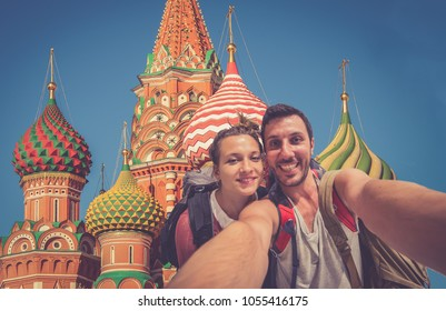 handsome young woman and man tourists takes selfie portrait on the Red Square in Moscow, Russia. Backpackers takes photo for travel blog and advertisement
