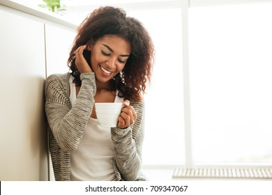 Handsome young woman in pajamas with cup of tea sitting on floor