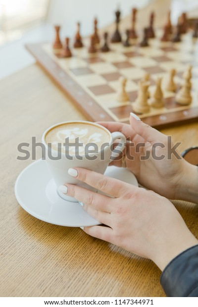 A handsome young woman sits at a wooden table in a loft-style cafe and drinks a cup of coffee or tea. She is inviting and cheerful, enjoying breakfast