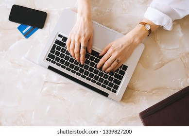 Handsome young woman typing at laptop keyboard. Work place concept, top view