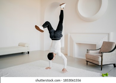 handstand, cardio warm-up exercise healthy lifestyle home workout. strong hardy athletic man doing sports fitness gymnastics, brunette