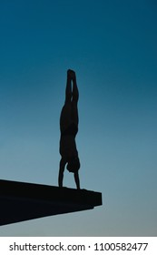 Handstand diver on board preparing to jump in dusk