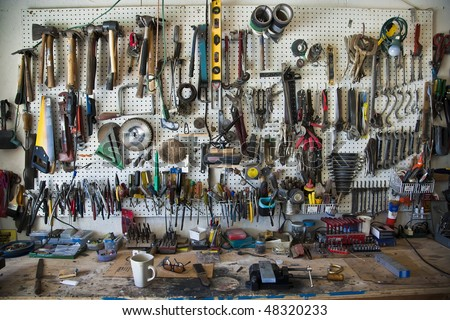 Hand-tools organized on a pegboard in a home shop above a workbench.