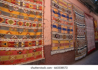 Handwoven Berber rugs hanging on a wall in an alley leading into the old town of Marrakech, Morocco.