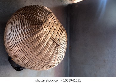A handwoven spherical basket hanging against the corner of a shadowed interior wall.