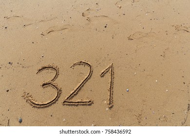 Handwrited number on the sand at the beach on beach background.