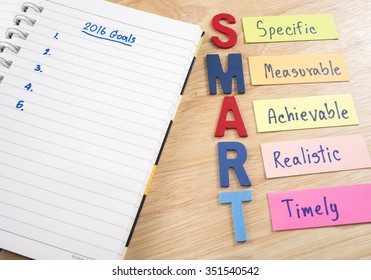 Handwriting 2016 Goals in notebook and word spell SMART Goals on wood background (Business Concept)