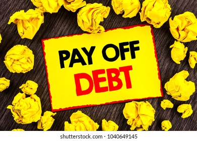 Handwriting Announcement text  Pay Off Debt. Conceptual photo Reminder To Paying Owed Financial Credit Loan Bills written Yellow Stikcy Note Folded Paper the wooden background