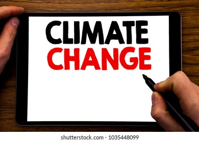 Handwriting Announcement text showing Climate Change. Business concept for Global Planet Warming Written tablet laptop, wooden background with businessman hand, finger writing on PC.