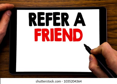 Handwriting Announcement text showing Refer A Friend. Business concept for Referral Marketing Written tablet laptop, wooden background with businessman hand, finger writing on PC.