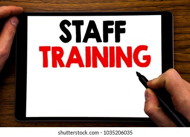Handwriting Announcement text showing Staff Training. Business concept for Teaching or Education Written tablet laptop, wooden background with businessman hand, finger writing on PC.