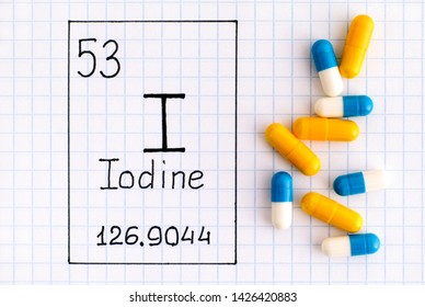 Handwriting chemical element Iodine I with some pills. Close-up.
