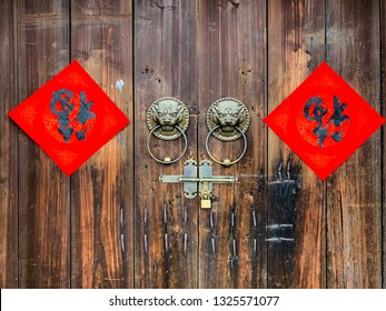 """The Handwriting Chinese blessing """"Fu"""" on the wooden door with traditional chinese bronze handle during the Chinese New Year."""