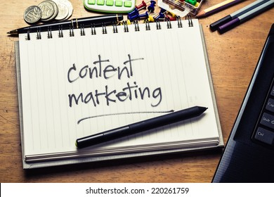 Handwriting of Content Marketing word in notebook on the wood table