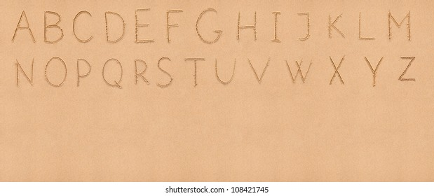 Handwriting English alphabet on flat sand with empty space appropriate as a background for your text