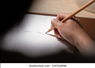 "Handwriting of ""I love you"" text on paper, people is using pencil to write it down on blank paper. Selective focus on the pencel's part and people's hand."