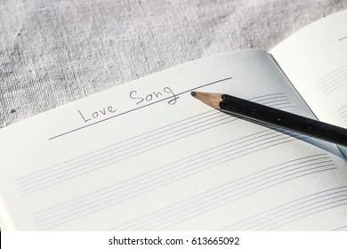 Handwriting 'Love Song' on music notebook with cotton fabric background
