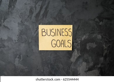 "handwriting of message ""BUSINESS GOALS"" on a sticky note paper on abstract concrete wall"