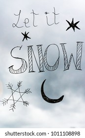 "Handwriting on a window saying ""let it snow""; Cloudy sky in the background"