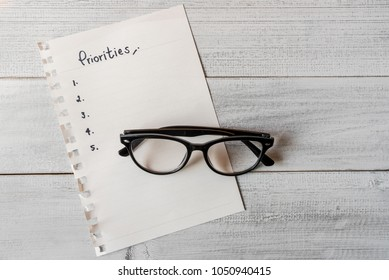 Handwriting priorities on white paper note with eyeglasses.