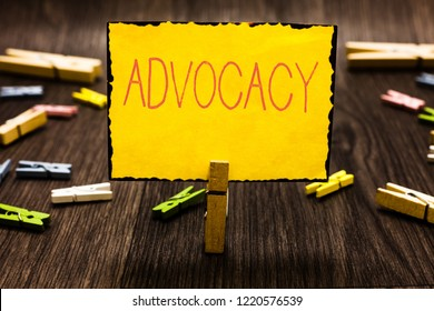 Handwriting text Advocacy. Concept meaning Profession of legal advocate Lawyer work Public recommendation Clothespin holding yellow paper note several clothespins wooden floor.