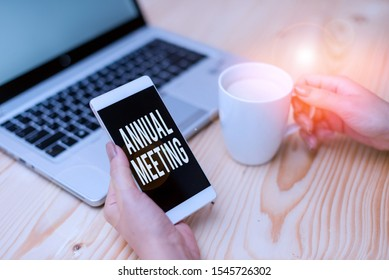 Handwriting text Annual Meeting. Concept meaning yearly meeting of the general membership of an organization woman laptop computer smartphone mug office supplies technological devices.