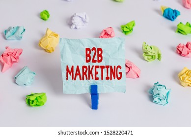 Handwriting text B2B Marketing. Concept meaning Partnership Companies Supply Chain Merger Leads Resell Colored crumpled papers empty reminder white floor background clothespin.