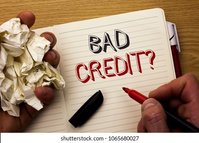 Handwriting text Bad Credit Question. Concept meaning Low Credit Finance Economic Budget Asking Questionaire written by Man on Notebook Book Holding Marker on the wooden background Pen next to it.