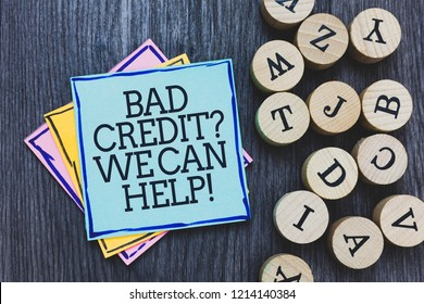 Handwriting text Bad Credit question We Can Help. Concept meaning Borrower with high risk Debts Financial Black wooden deck written sticky note beside some round woody alphabets.