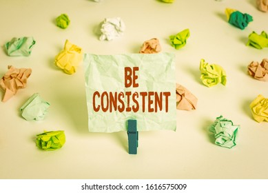 Handwriting text Be Consistent. Concept meaning Uniform Persistent Firm Unalterable Even Unchanging Rapport Colored crumpled papers empty reminder white floor background clothespin.